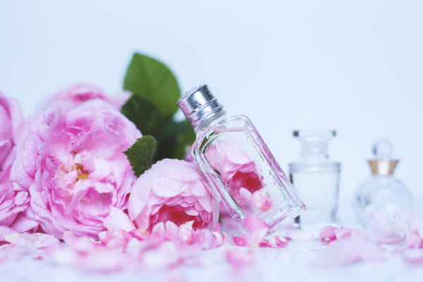 Small Perfumes With Pink Flowers On Light Background